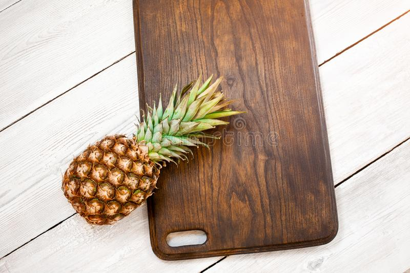 Fresh ripe pineapple on a white wooden background, top view. From above stock photos