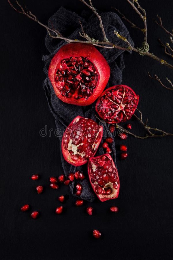 Fresh ripe pomegranate on a napkin and slate plate kitchen table stock image