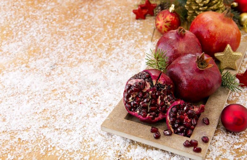 Fresh ripe pomegranates on wooden background and Christmas decoration. stock photos