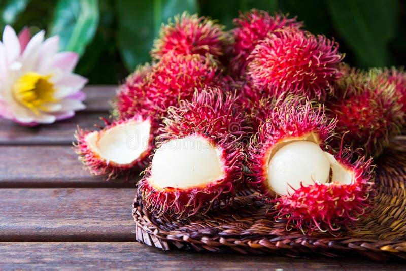 Fresh ripe rambutans on wooden background. Delicious rambutan sw stock images