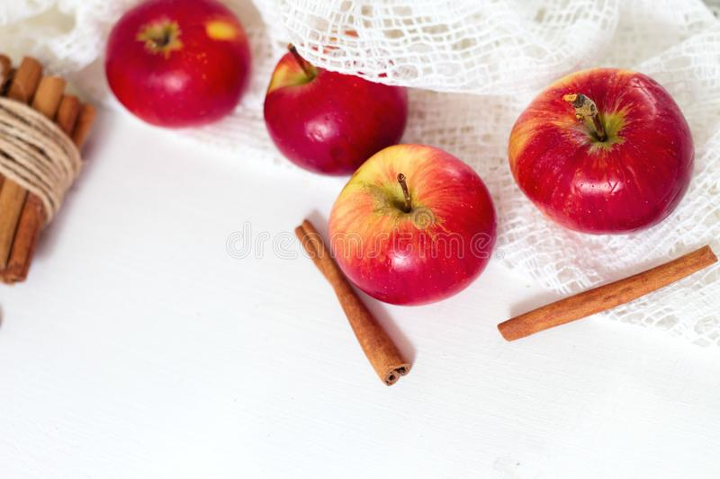 Fresh ripe red apples and cinnamon sticks on white wooden background royalty free stock photos