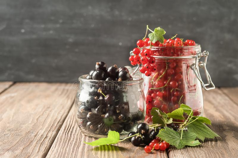 Fresh ripe red black currant berry in various glass jars on a dark background. Horizontal frame. Selective focus. stock photo