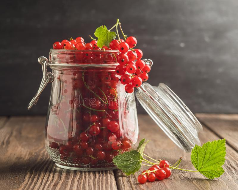 Fresh ripe red currant berry in a glass jar on a wooden table. Selective focus. royalty free stock image