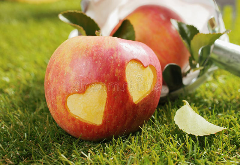 Fresh apple with incised hearts stock photos