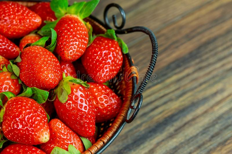 Fresh ripe strawberries in a basket on wooden background royalty free stock image