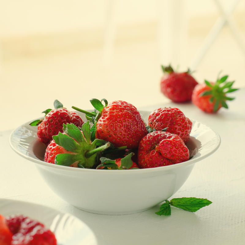 Fresh ripe strawberries in bowl on white background, square, toned stock images