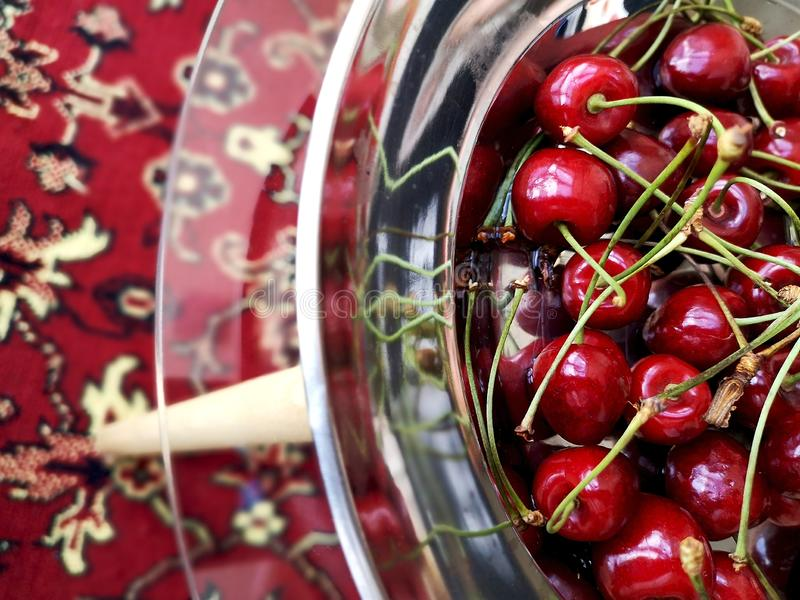 Sweet ripe cherries in a metal plate on a glass table. royalty free stock images