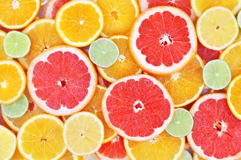 Fresh ripe sweet citrus fruits colorful background: orange, grapefruit, lime, lemon. Fresh ripe sweet cut citrus fruits colorful background: orange, grapefruit royalty free stock photography