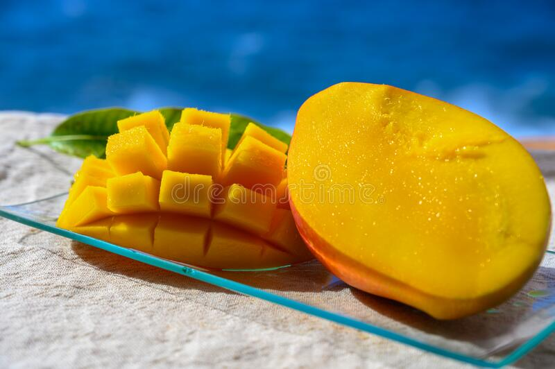 Fresh ripe sweet yellow mango fruit served on glass plate with blue seaview background royalty free stock photo