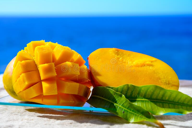 Fresh ripe sweet yellow mango fruit served on glass plate with blue seaview background royalty free stock photography