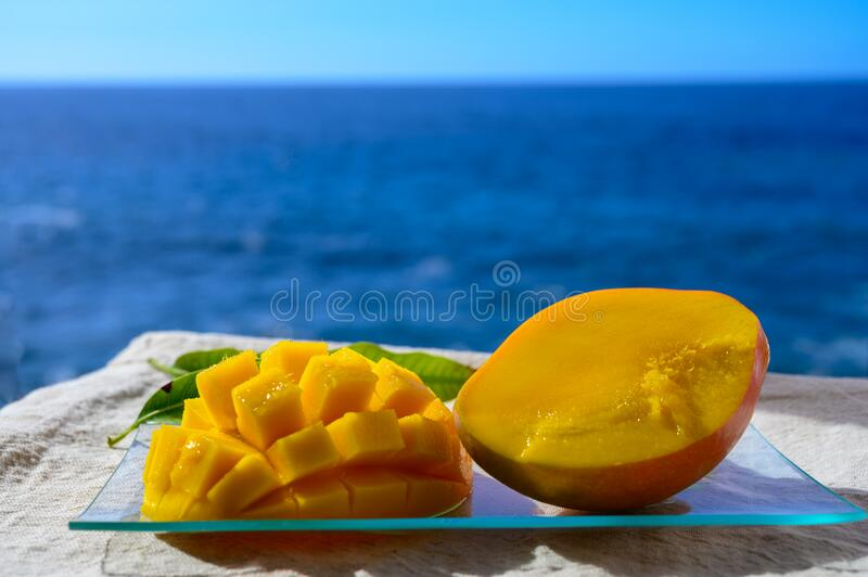Fresh ripe sweet yellow mango fruit served on glass plate with blue seaview background royalty free stock images
