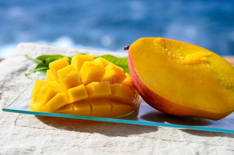 Fresh ripe sweet yellow mango fruit served on glass plate with blue seaview background stock photos