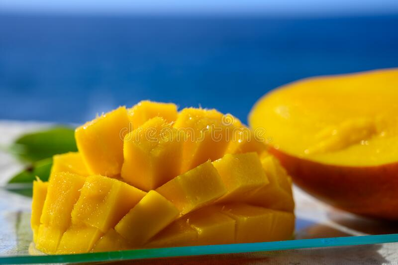 Fresh ripe sweet yellow mango fruit served on glass plate with blue seaview background stock images