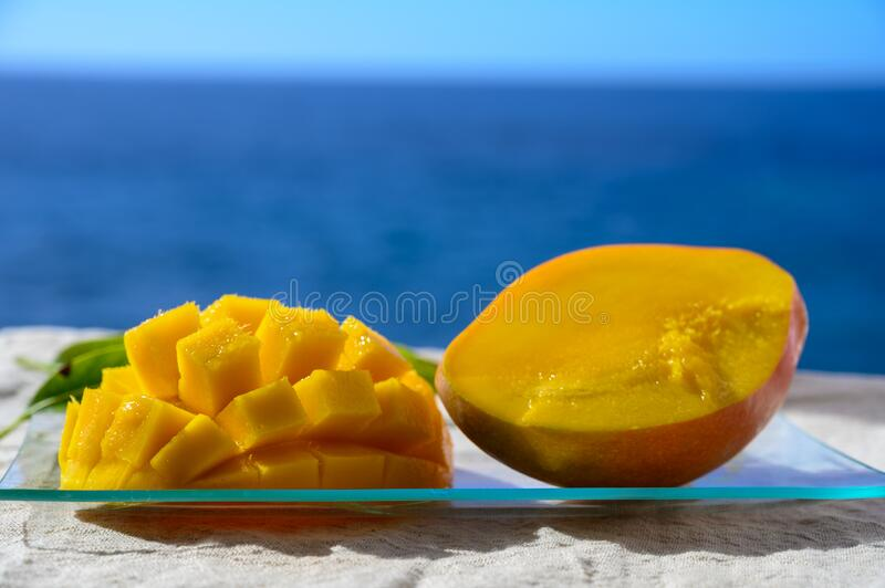 Fresh ripe sweet yellow mango fruit served on glass plate with blue seaview background stock photo