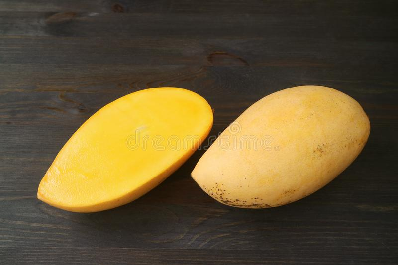 Fresh Ripe Thai Nam Dok Mai Mango Whole Fruit and Cut in Half on Dark Brown Wooden Background royalty free stock photo