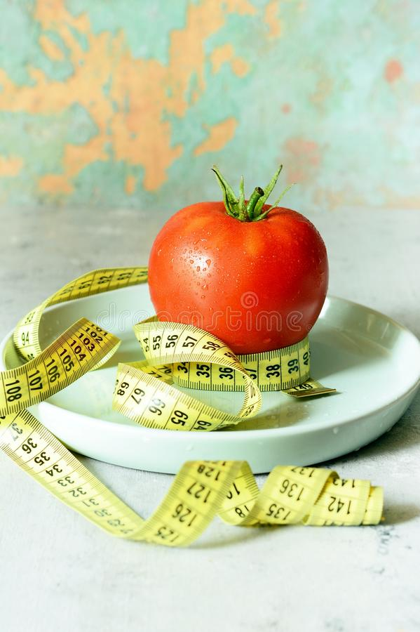 Fresh ripe tomato on a gray background. Tape for measuring body volume. Diet and fitness. stock images