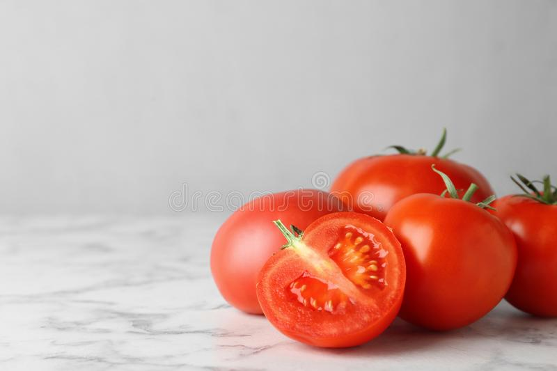 Fresh ripe whole and cut tomatoes on white marble table. Space for text stock photo