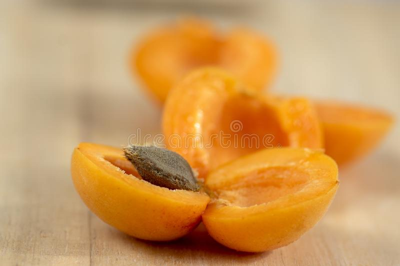 Fresh ripened apricots cut in halves with stone on wooden table in sunlight, edible tasty fruits ripening in early summer. Fresh ripened apricots cut in halves royalty free stock image