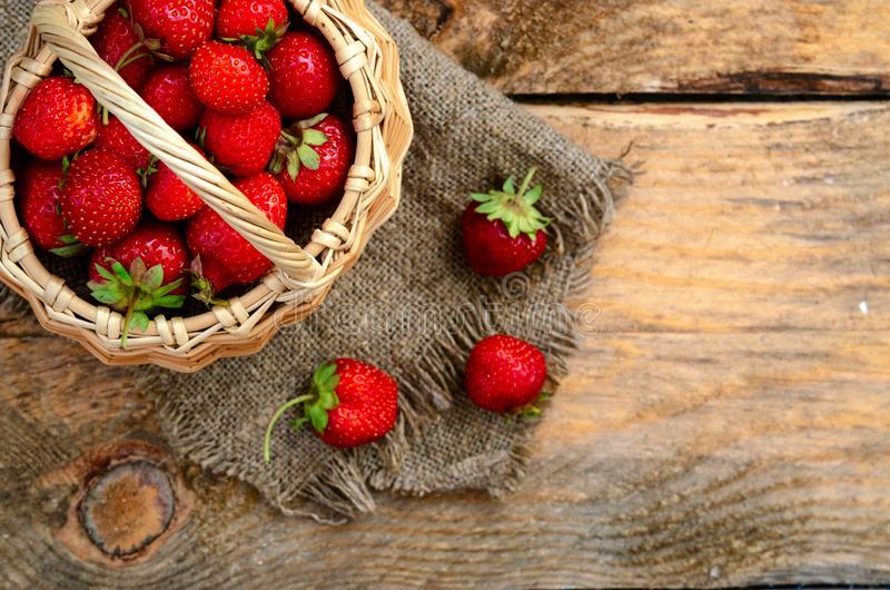 Fresh ripened strawberries in basket full isolated on wood stock images