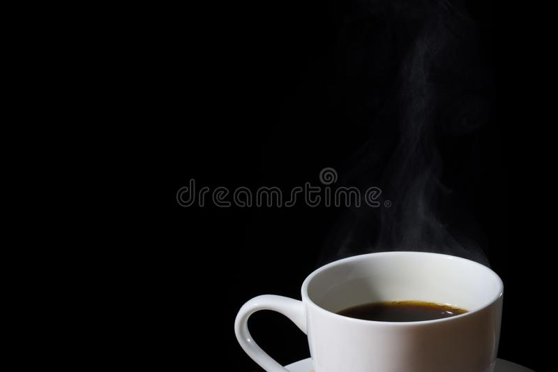 White cup of brewed coffee with steam or vapor and isolated in black. A fresh roasted brewed coffee in a white cup with steam and vapor and scattered coffee stock image