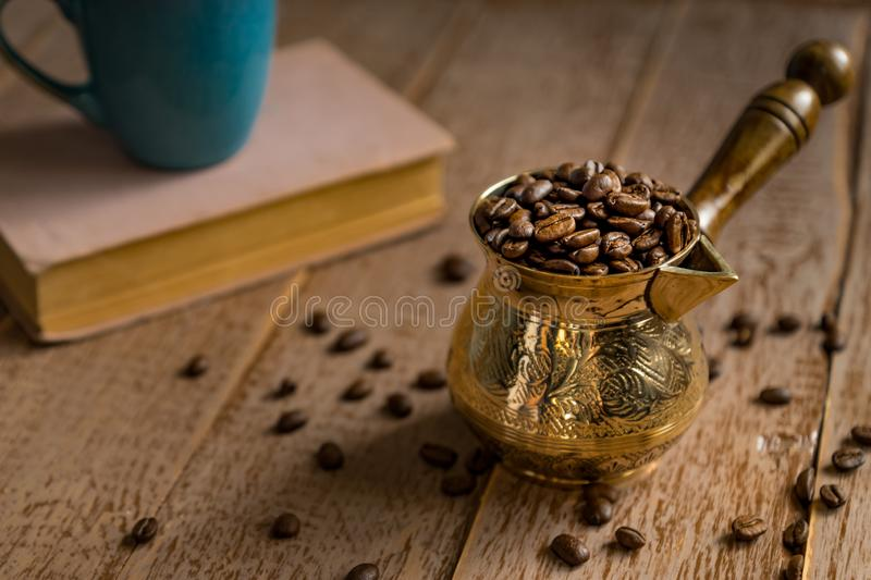 Fresh roasted coffe beans in  cezve traditional turkish coffee pot closed book and cup on wooden table.  stock image