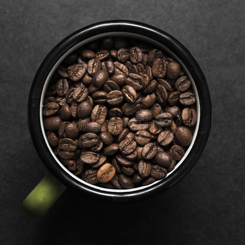 Fresh roasted coffee beans in coffee cup. Fresh roasted coffee beans in metal coffee cup stock image