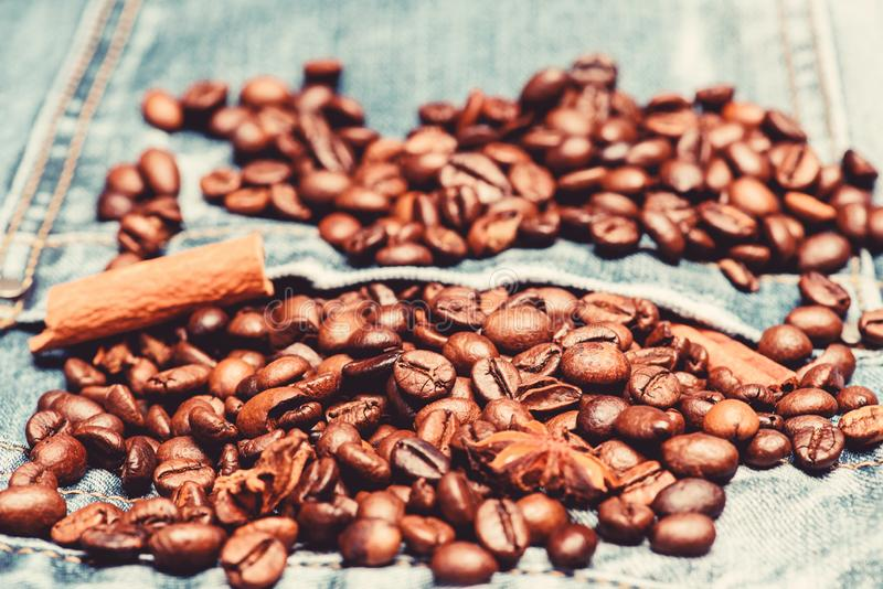 Fresh roasted coffee close up. Beans and spices in jeans pocket. Coffee for inspiration and energy charge. Coffee shop. Or store. Degree of roasting coffee stock image