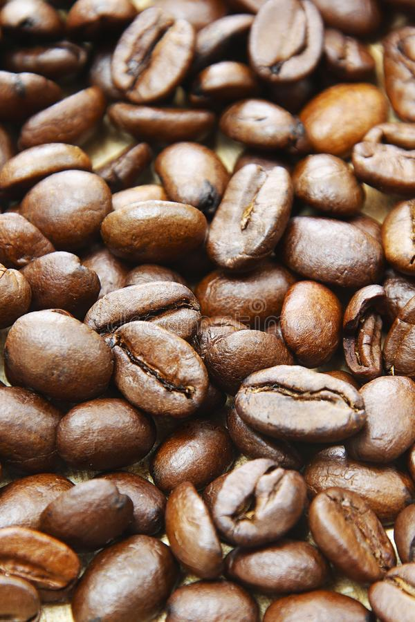 Roasted coffee beans closeup background espresso black closeup. Fresh Roasted italian coffee espressobeans on a wooden plate  as background whole beans royalty free stock images