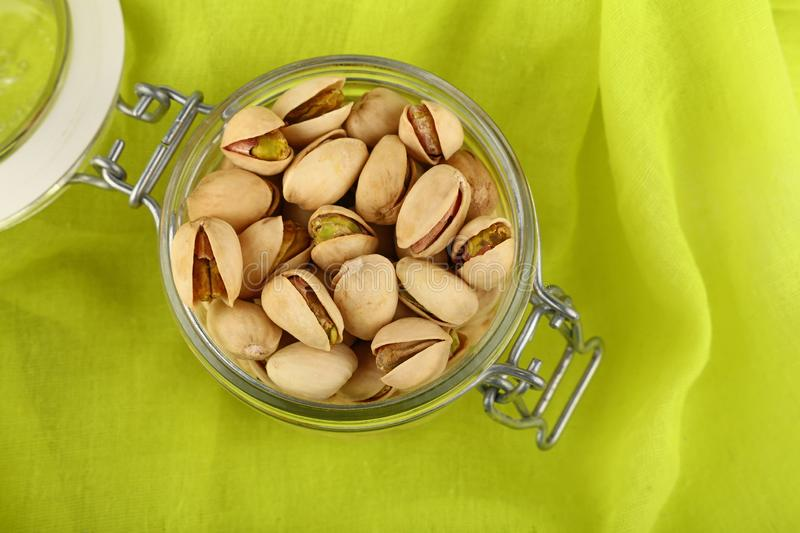 Fresh roasted pistachio nuts in glass jar. Close up fresh roasted pistachio nuts in glass jar over green yellow background, elevated, high angle top view stock photo