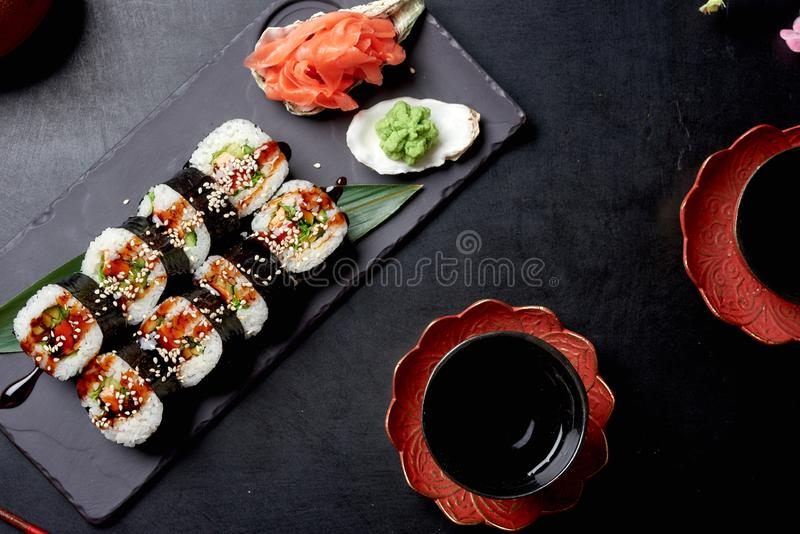 Fresh rolls in nori seaweed with wasabi, pickled ginger and soy sauce. Asian cuisine, traditional dish - sushi. Fresh rolls in nori seaweed with avocado, shrimp royalty free stock photography