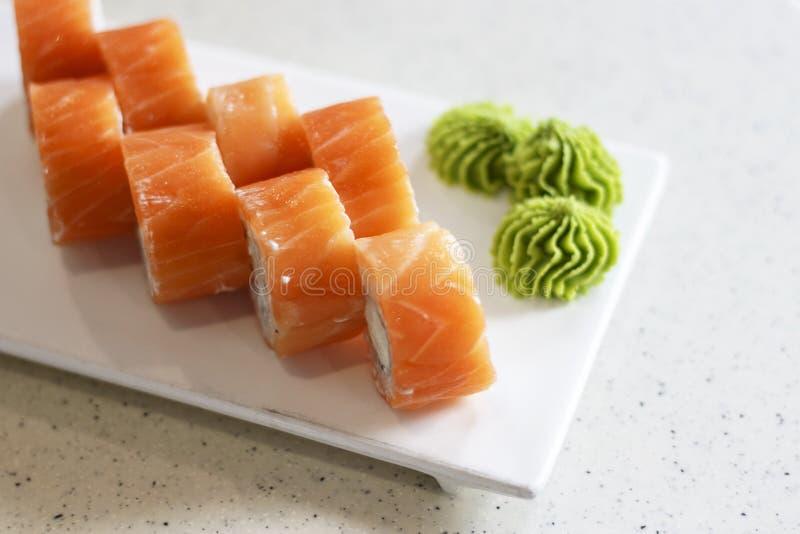 Fresh rolls philadelphia and wasabi sauce on rectangular white plate close-up royalty free stock photos