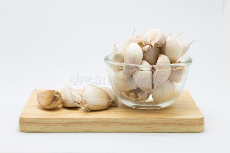 Fresh rood garlic on wooden board. On glass cup, on white background royalty free stock photo