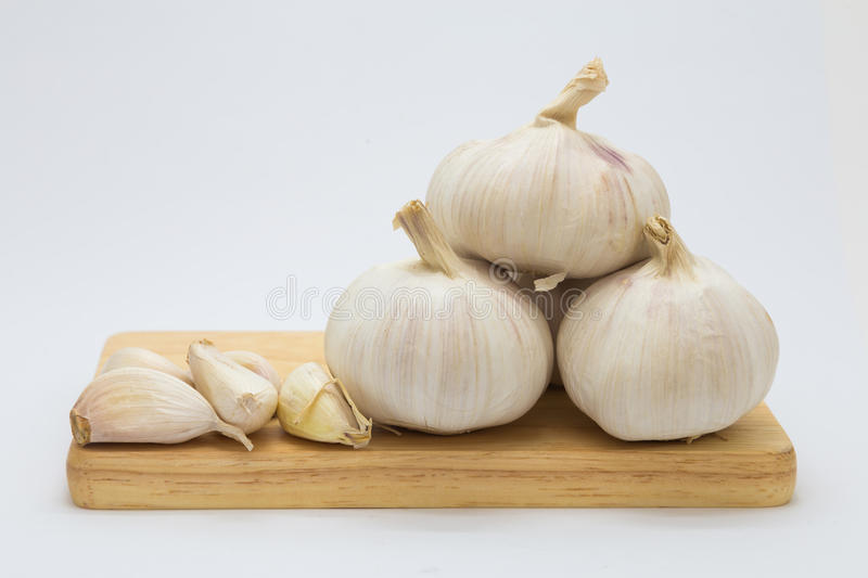 Fresh rood garlic on wooden board. On white background stock images