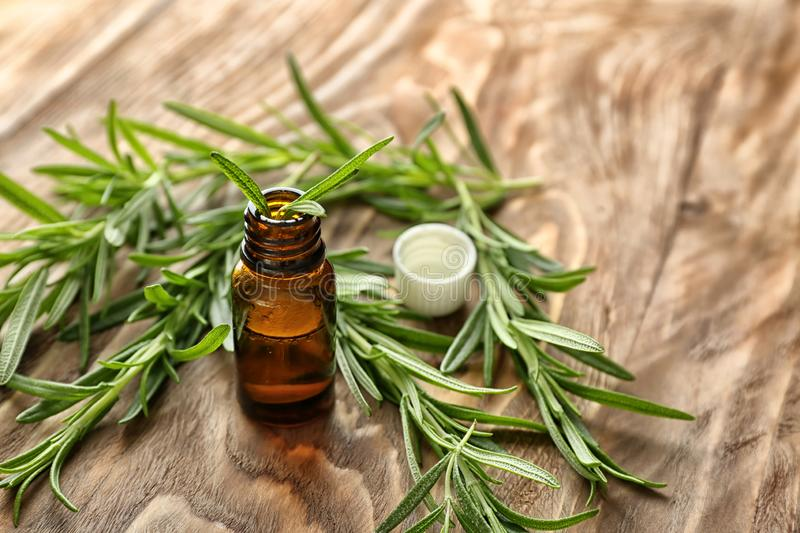 Fresh rosemary and bottle of essential oil on wooden background stock image