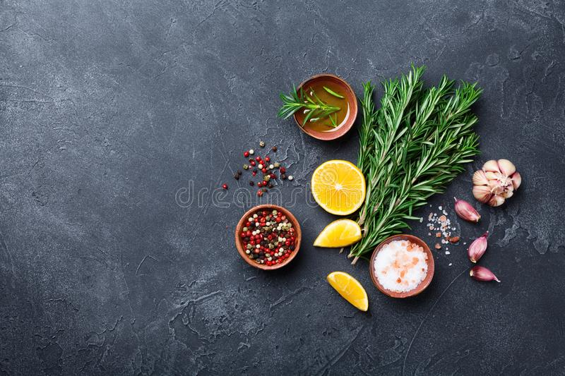 Fresh rosemary and mixed spices on black stone table top view. Ingredients for cooking. Food background. royalty free stock photography