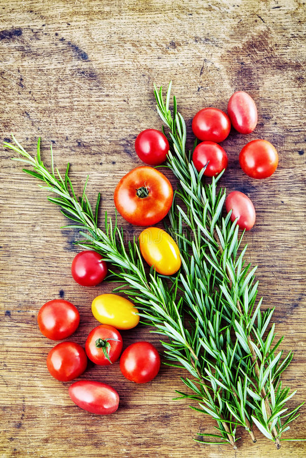 Fresh rosemary with tag, red and green tomatoes on rustic wooden stock image