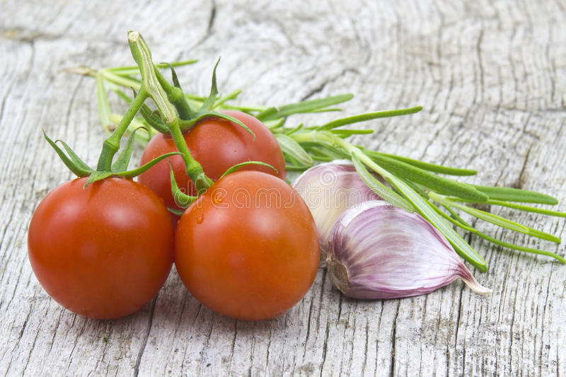 Fresh rosemary, tomatoes and garlic. On old wooden background royalty free stock image