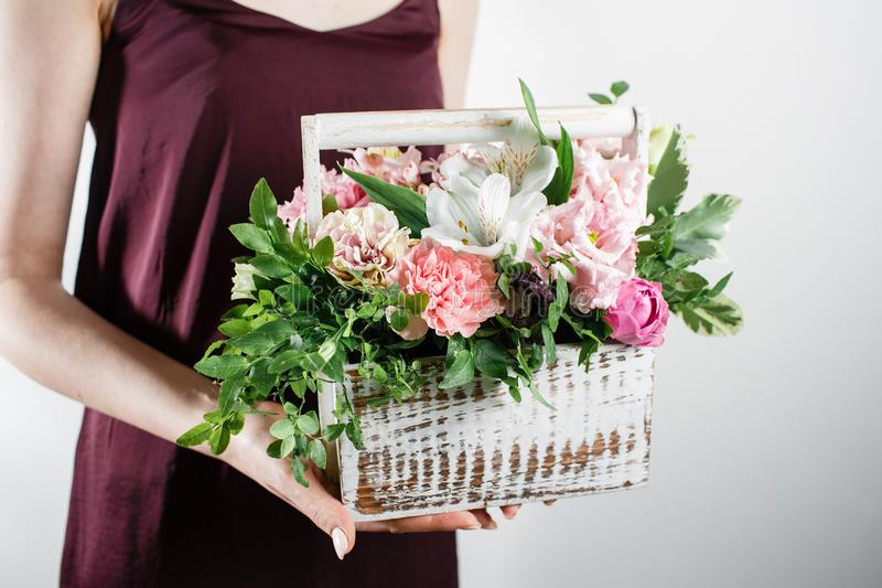 Fresh eustoma and Alstroemeria in box on white wooden background. Vintage style. Selective focus. stock photo