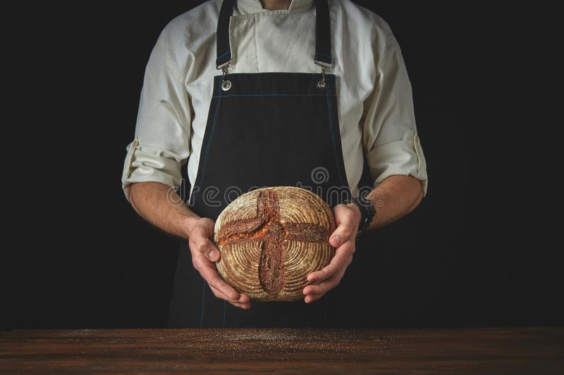 Fresh round bread male hands holding royalty free stock photo