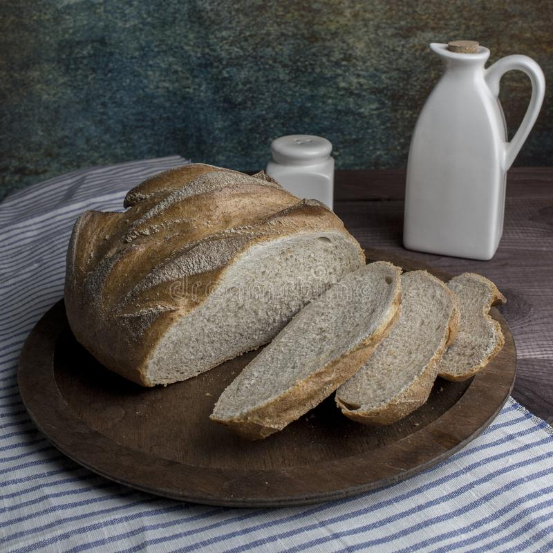 Fresh round bread with slices on a wooden tray. Rustic still life bread salt butter, tableware flax linen tablecloth stock photo
