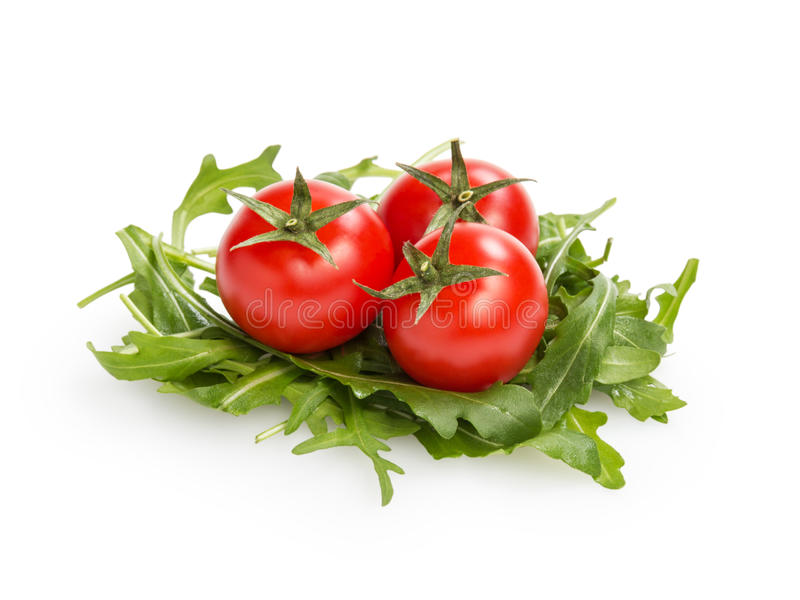 Fresh rucola leaves with cherry tomatoes. Isolated on white royalty free stock photo