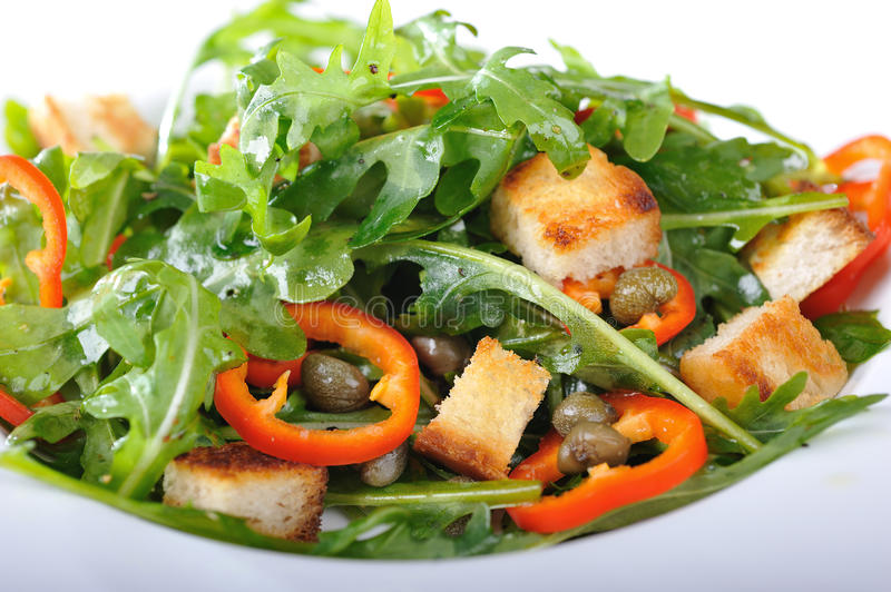 Fresh rucola salad. With paprika and capers and roasted bread stock photography