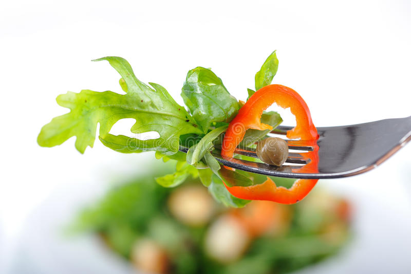 Fresh rucola salad. With paprika and caperon a fork royalty free stock photography
