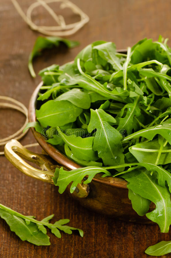 Fresh rucola salad leaves. In bowl on wooden background stock image