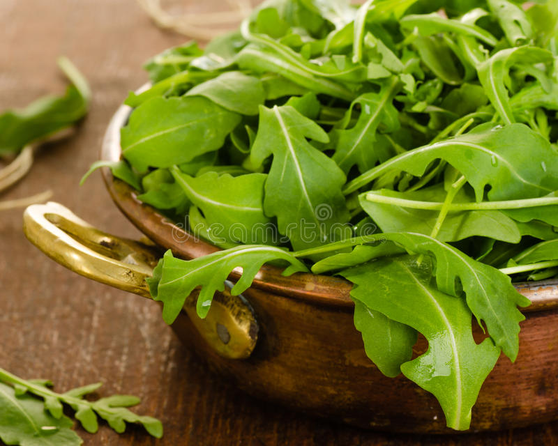 Fresh rucola salad leaves in bowl. On wooden background stock image