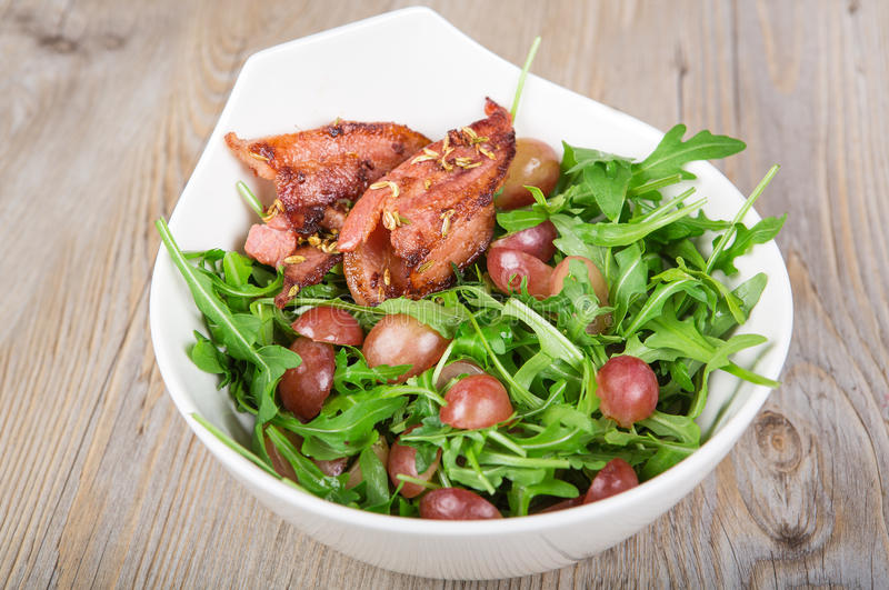 Fresh rucola salad with red grapes. On wooden table stock photography
