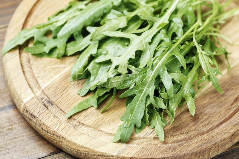 Fresh rucola salad. On a wooden background. A useful vegan product on a cutting board stock image