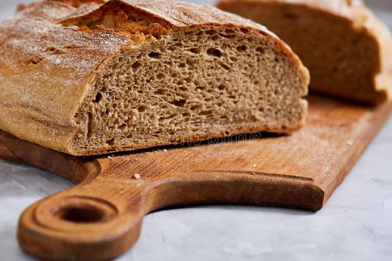 Fresh rye bread loaf on a wooden chopping board over white textured background, shallow depth of field royalty free stock images