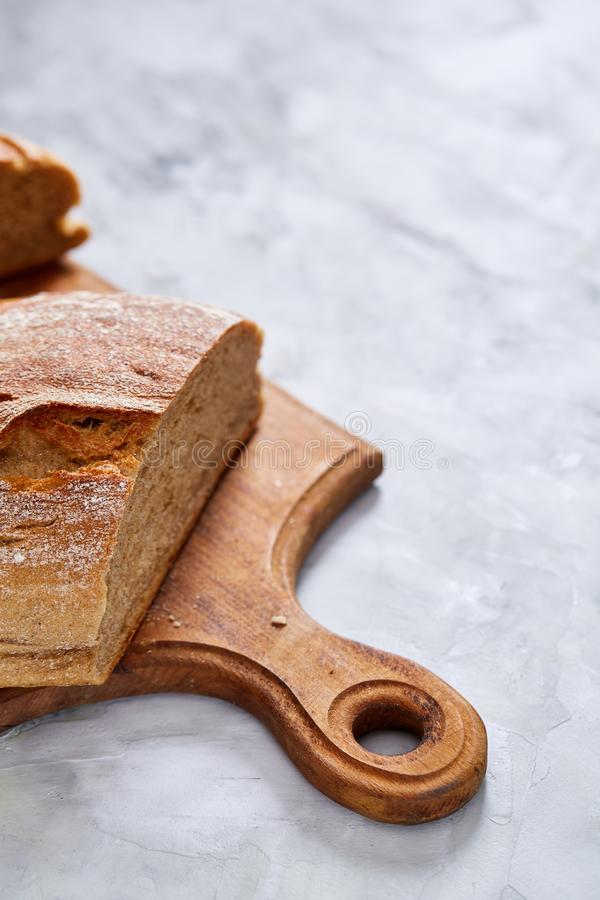 Fresh rye bread loaf on a wooden chopping board over white textured background, shallow depth of field stock images