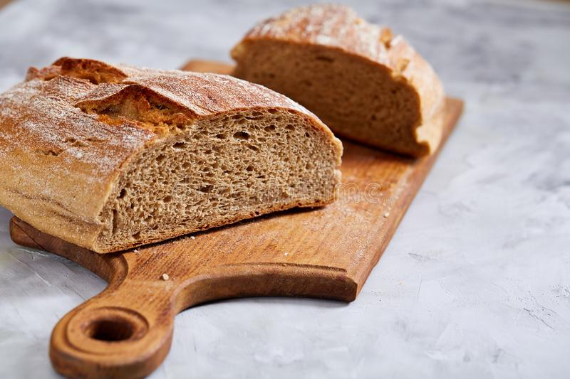 Fresh rye bread loaf on a wooden chopping board over white textured background, shallow depth of field stock photography